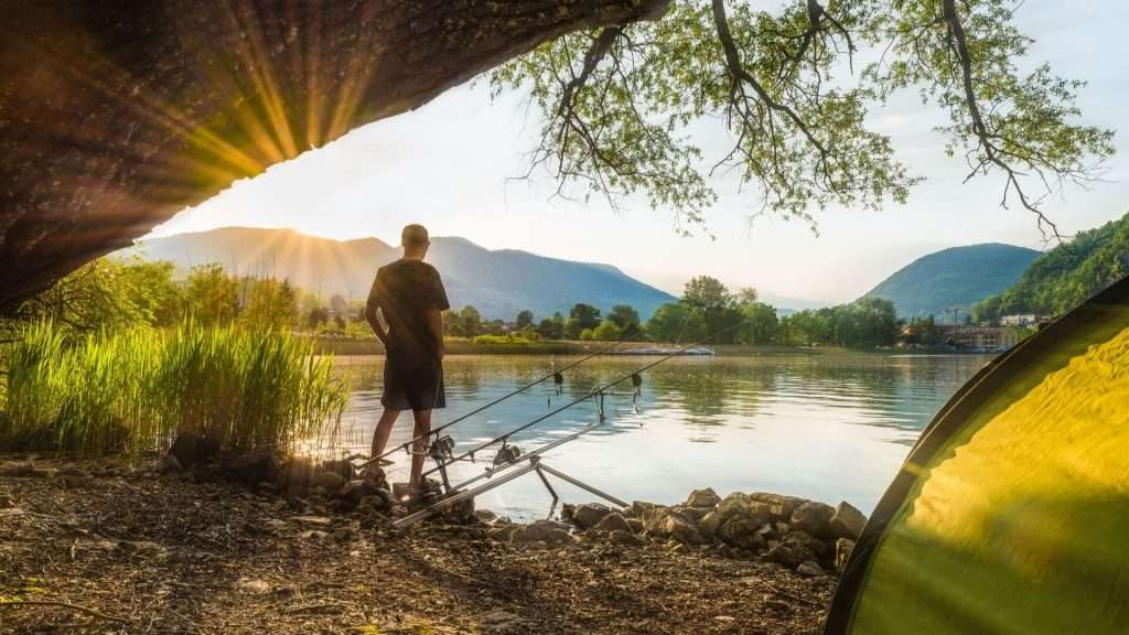 man standing by a lake carp fishing
